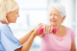 Young female therapist assisting senior woman in lifting dumbbell at nursing home. Horizontal shot.